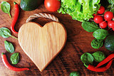 Healthy food ingredients background. Vegetables,herbs and cutting board on wooden background. Top view.