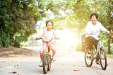Grandmother and granddaughter biking outdoor.