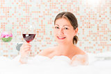 portrait of a happy girl in a bath with a glass of drink