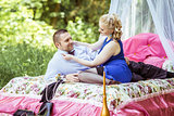 A couple on bed in meadow