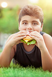 Teen boy eating burger
