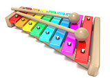 Xylophone with rainbow colored keys and with two wood drum stick