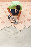 Man cutting ceramic floor tiles with manual cutter