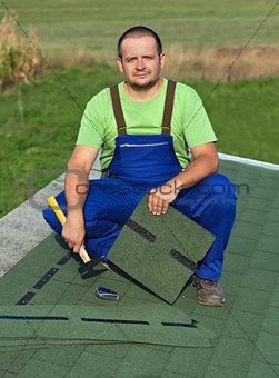 Man on the roof fastening bitumen shingles on annex building
