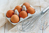 Brown eggs with stainless steel whisk.