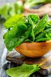 Wooden bowl with spinach leaves.