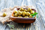 Green olives and parsley in a wooden bowl.