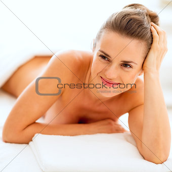 Portrait of happy young woman laying on massage table