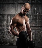 Athletic man training biceps on grunge background