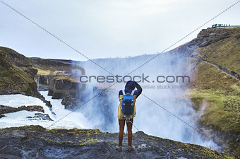 A man stands on the edge of a waterfall Gullfoss and takes pictures of him