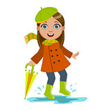 Girl In Green Beret With Umbrella, Kid In Autumn Clothes In Fall Season Enjoyingn Rain And Rainy Weather, Splashes And Puddles