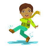 Boy Kicking Water With Foot, Kid In Autumn Clothes In Fall Season Enjoyingn Rain And Rainy Weather, Splashes And Puddles
