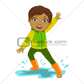 Boy In Green And Yellow Jacket, Kid In Autumn Clothes In Fall Season Enjoyingn Rain And Rainy Weather, Splashes And Puddles