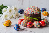 Easter cake kulich with eggs and spring flowers on light wooden background