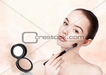 Beautiful girl holding makeup brush for foundation