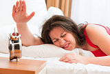 irritated woman off the alarm that prevent sleep