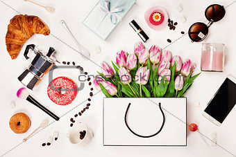 Top view of spring flowers, coffee, mobile phone, croissants, gi