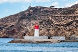 Red and white lighthouse near the fort of Christmas and the seaport. Cartagena, Spain.