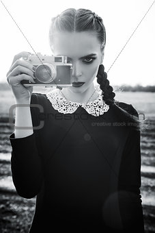 Beautiful sad young girl photographing on vintage film camera. Black and white