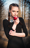 Outdoor portrait of cute young girl in old-fashioned dress eating red apple