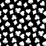 Seamless pattern background of white poker suits - hearts, clubs, spades and diamonds - on black background. Casino gambling theme vector illustration