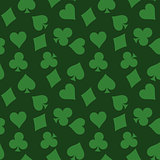 Seamless pattern background of green poker suits - hearts, clubs, spades and diamonds - on green background. Casino gambling theme vector illustration