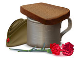 War mug with water, bread, red carnation flower and military cap. Symbol of memory of dead