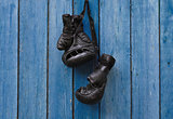 Black vintage boxing gloves hanging on an old rusty nail