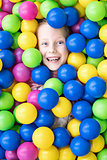 Smiling child in colored balls