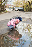 Two children look in a puddle