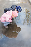 Two children near a puddle