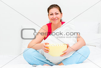 smiling brunette with a bowl of popcorn watching tv