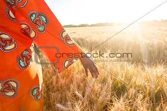 African woman in traditional clothes walking with her hand on a