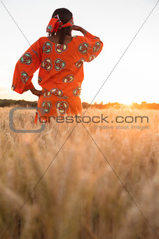 African woman in traditional clothes looking in a field of crops