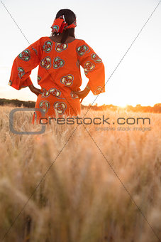 African woman in traditional clothes walking in a field of crops