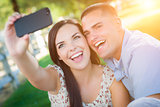 Happy Mixed Race Couple Taking Self Portrait with A Smart Phone