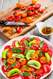 tomato, kiwi fruit and cheese brie salad decorated with mint lea