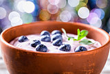 yogurt with blueberries and mint, bokeh background. selective fo