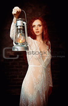 Portrait of lovely young redhead woman with kerosene lamp