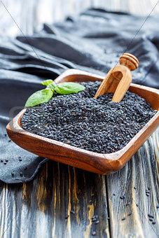 Black sesame seeds in a wooden bowl.