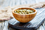 Pumpkin seeds in a wooden bowl.