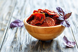Sun-dried tomatoes and basil leaves in a wooden bowl.ыя