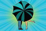 Man and woman kissing behind umbrella