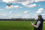 man operating of flying drone quadrocopter at the green field