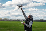 man holding of flying drone quadrocopter at the green field