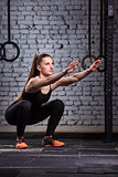 Muscular beautiful woman doing squats in brutal interior. Crossfit.