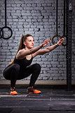 Muscular beautiful woman doing squats in brutal interior. Crossfit.