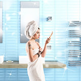 Woman with tattoo washes in the bathroom wrapped in a towel