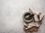 Empty granite mortar and kitchen towel on a gray textured background