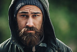 Outdor porttrait of a handsome brutal bearded man with dark beard and mustache dressed in winter clothes, covered with frost. Man wear coat hat and hood. look like hipster.